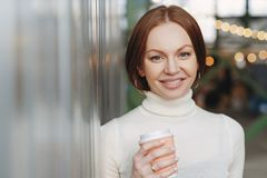 Good looking young female dressed in casual white turtleneck sweater, holds paper cup of aromatic cappucino or coffee, looks stock photography