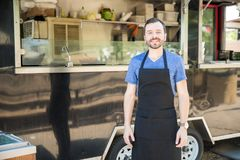 Male food truck owner. Good looking young male cook standing outside with his food truck on the background stock photos