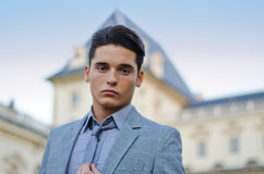 Good looking young male model and elegant palace. Portrait of handsome young male model on river banks looking in camera Stock Photography