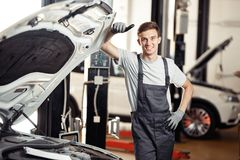 A good-looking young man is behind the car he is repairing royalty free stock photos
