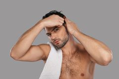 Perfect man. Good looking young man combing his hair while standing against grey background Stock Photography