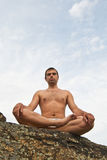 Good-looking young man doing yoga on stone Royalty Free Stock Photography