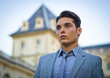 Good looking young man and elegant palace. Portrait of handsome young male model on river banks Stock Photo