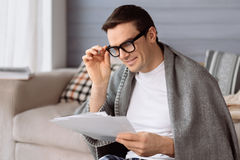 Good looking young man fixing his glasses. Involved in work. Good looking nice pleasant man fixing his eyeglasses and holding some documents while reviewing them Stock Photography