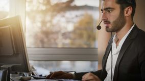 Young telemarketer, help desk assistant or customer service worker. Good looking young man with headset working as help-desk assistant, customer service, help Stock Photos