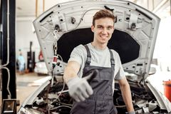 A good-looking young man is at his work: car repair service royalty free stock photos