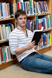Good-looking young man holding a book on the floor Stock Images