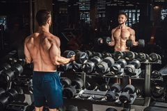 Good looking young man lifting dumbbells and working on his biceps in front of the mirror at the gym. Good looking young man lifting dumbbells and working on his Stock Images