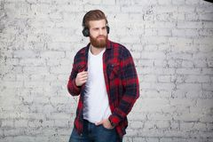 Good looking young man listening music and looking away while standing against white brick wall. NHe is wearing a plaid shirt and a white T-shirt stock photography