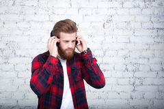 Good looking young man listening music and looking away while standing against white brick wall stock photos