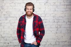 Good looking young man listening music and looking away while standing against white brick wall royalty free stock photo