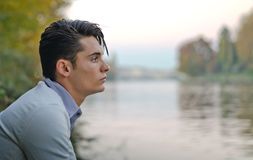 Good looking young man outdoors in nature. Profile portrait of handsome young male model on river banks Royalty Free Stock Photography
