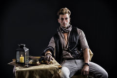 Good Looking Young Man in Pirate Fashion Outfit Sitting next to Table Royalty Free Stock Photography