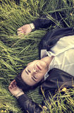 Good looking, young man relaxing lying on grass Stock Image