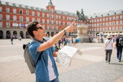 Good looking young man traveler holding up a map in madrid. Hipster young man traveler traveling in Madrid holing up a map in the plaza major in tourist travel Royalty Free Stock Photo