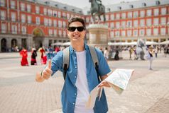 Good looking young man traveler holding up a map in madrid. Hipster young man traveler traveling in Madrid holing up a map in the plaza major in tourist travel Royalty Free Stock Image