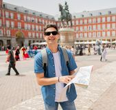 Good looking young man traveler holding up a map in madrid. Hipster young man traveler traveling in Madrid holing up a map in the plaza major in tourist travel Stock Photography