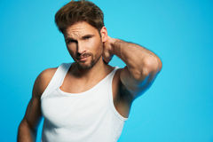 Good looking young man in white undershirt against blue background. Fashion portrait of a gorgeous male model in white undershirt posing stock image