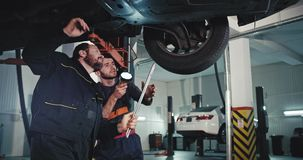 Good looking young mechanic guy and main mechanic mature man checking the problem of damaged car they analyzing the