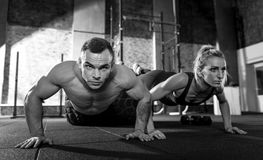 Good looking young people working out together. Bodybuilders workout. Good looking sporty young people putting their legs on a giant tire and doing push ups Royalty Free Stock Photo