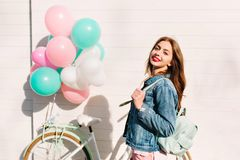 Good-looking young woman in denim jacket with stylish backpack going to bike ride around city in morning. Close-up