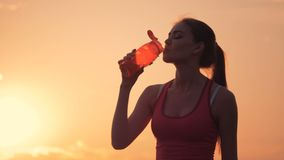 Good-looking young woman is drinking from an orange bottle in beams of sun. 4K stock video footage