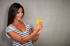 Good-looking young woman holding cell phone Stock Images