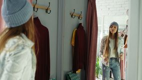 Good-looking young woman is trying on clothes in fitting room. She is watching herself in mirror, posing and moving stock footage