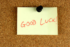 Good Luck. Yellow small sticky note on an office cork bulletin board. Good luck wishes stock image