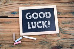 Free Good Luck. Blackboard And Old Wooden Table Royalty Free Stock Image - 123012816