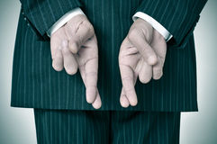 Good luck. A man wearing a suit crossing his fingers in his back Stock Image