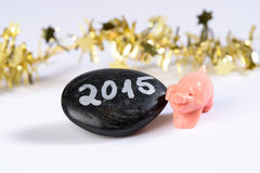 Good Luck Pig, New Year 2015. Black Stone with date 2015 next to a pink piggy, that symbolizes congratulations for the year change Stock Photography