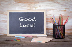 Good luck text on a blackboard. Old wooden table with texture Stock Images