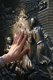 Good luck touch. Statue of St. John of Nepomuk on Charles bridge in Prague made by Jan Brokof in 1683. Women is touching for a good luck bronze plate of St. John Stock Images