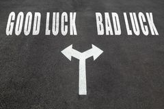 Good luck vs bad luck choice concept. Two direction arrows on asphalt Royalty Free Stock Image