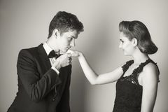Good manners - to kiss the girl`s hand?. Young men kisses a girl`s hand in an elegant dress Stock Images
