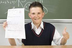 Good mark. Young, smiling boy sitting at dest in front of blackboard with test in hand. Thumb up, front view Stock Photography