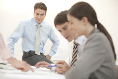 Good meeting. Four people in a business meeting, sitting on desk Stock Photography