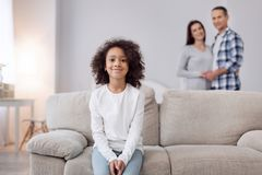 Glad girl sitting on the sofa. Good mood. Attractive cheerful curly-haired girl smiling and sitting on the couch and her parents standing in the background Stock Photos
