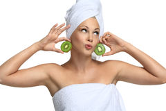 Good mood after bathing - funny girl. Beautiful blonde girl in towwel with kiwi - on white Stock Image