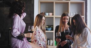 Good mood beautiful ladies enjoying the time together while celebrating bachelorette party at home in a modern studio. Holding wine glasses and moving funny in stock video