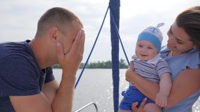 Good mood of friendly family on vacation to river, young mom and dad played with baby on sea in boat, stock video footage