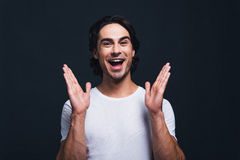 Always in good mood. Happy young man gesturing and looking at camera while standing against grey background Royalty Free Stock Photos