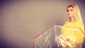Happy woman wearing raincoat holding transparent umbrella. Good mood during rainy day. Happy blonde woman wearing yellow raincoat holding transparent umbrella Royalty Free Stock Photo