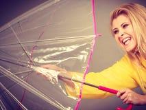 Happy woman wearing raincoat holding transparent umbrella. Good mood during rainy day. Happy blonde woman wearing yellow raincoat opening transparent umbrella Royalty Free Stock Image