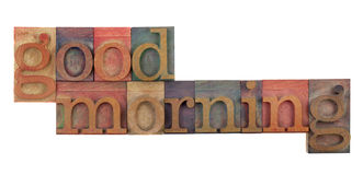 Good morning. Greeting in vintage wood letterpress type blocks, stained by color ink, isolated on white Royalty Free Stock Image