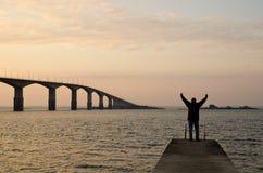 Good morning!. A man streches his arms in the morning sun at a long bridge Stock Photos
