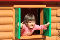 Good morning. Baby girl opens the windows of her house Royalty Free Stock Photo