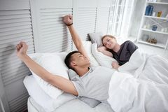 Merry satisfied gay couple waking up. Good morning. Appealing glad gay couple smiling while resting in bed and guy stretching Royalty Free Stock Images