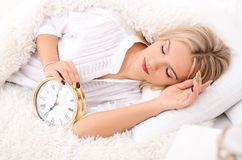 Good morning attractive young woman. Soon to wake up for sleeping attractive young woman with alarm clock Royalty Free Stock Photography